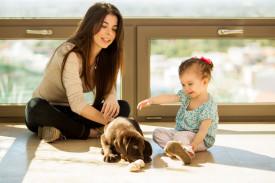 Mutter mit Kind und Hund auf Fliesenboden