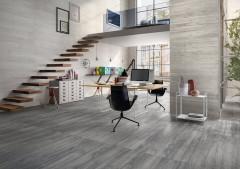 Arbeitszimmer im großzügigen Loftstyle mit Wand- und Bodenfliesen in Betonoptik