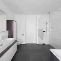 Kontrastreiche Badgestaltung mit schwarzen und weißen Fliesen.