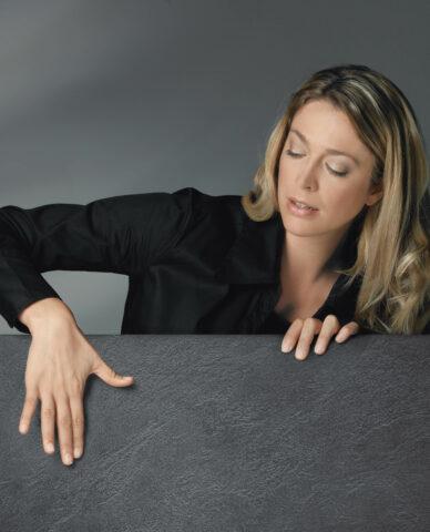Frau streicht mit den Händen über anthrazitfarbene Fliese