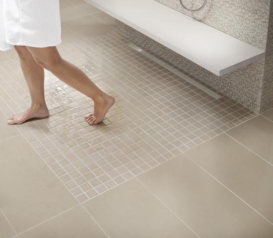 Eine Person im Bademantel läuft über einen Fliesenboden im Badezimmer