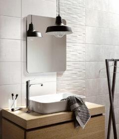 Perfekter Landhausstil: Cremefarbene Wandfliesen im Bad mit strukturierter Oberfläche, davor ein Waschtisch aus Holz