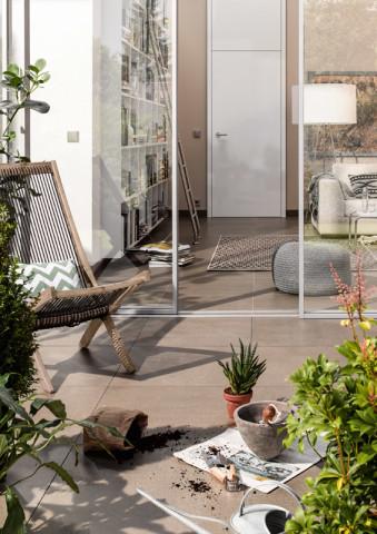 Cremefarbener Fliesenboden im Wintergarten mit Topfpflanzen im Vordergrund sowie Blick ins Wohnzimmer